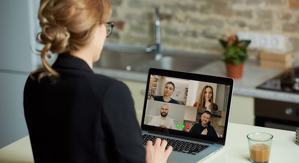 Woman with laptop attending a virtual meetup